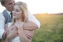 bride and groom lovingly hugging.