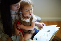 a mother reading a book to her daughter