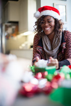 A smiling woman wearing a santa hat and wrapping Christmas presents