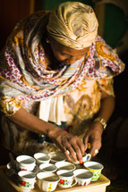 A woman in Ethiopia arranging tea cups