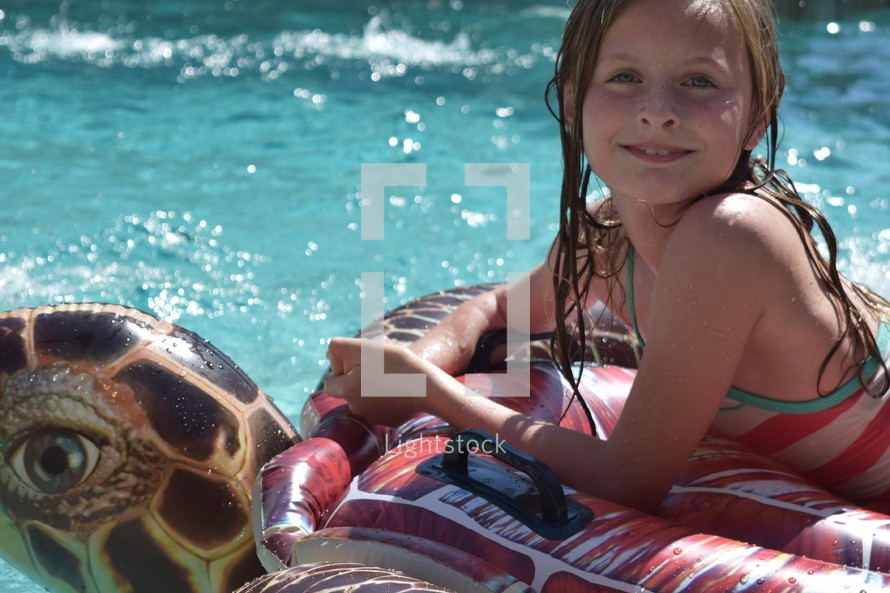 a little girl on a pool float in summer