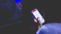 a person reading a Bible app on their phones  during a worship service
