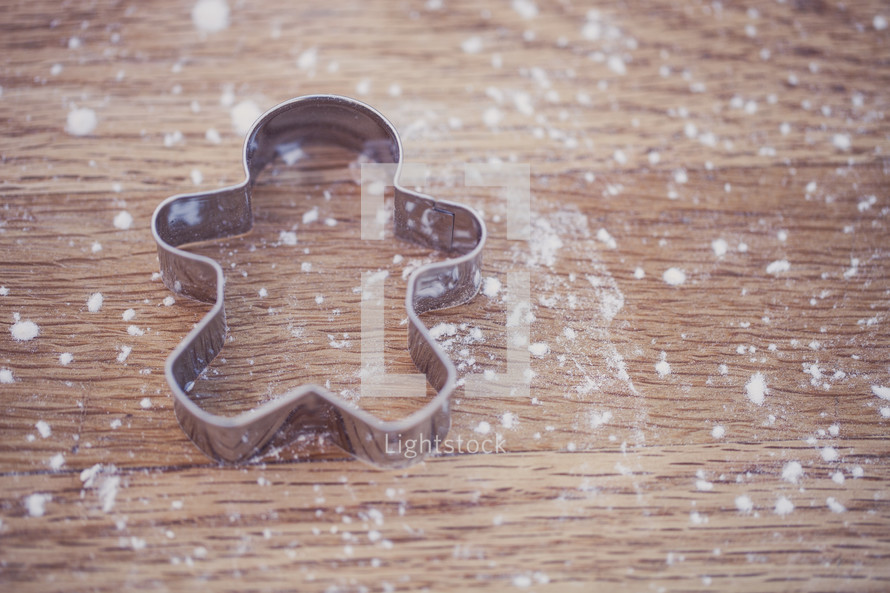 flour on a table and gingerbread man cookie cutter