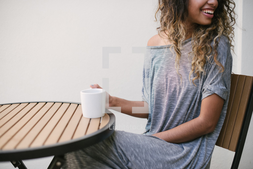 woman sitting at an outdoor table drinking coffee