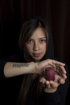 woman with a tattoo of the word Forgiven on her arm holding a candle