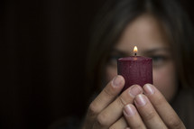 woman holding a red burning candle