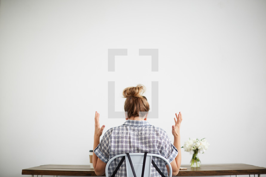 a woman sitting at a computer desk with her hands up