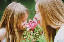 Mother and daughter smelling a bouquet of flowers.