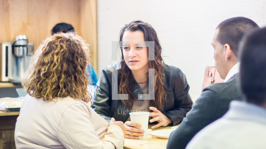 people sitting at tables having conversations after church
