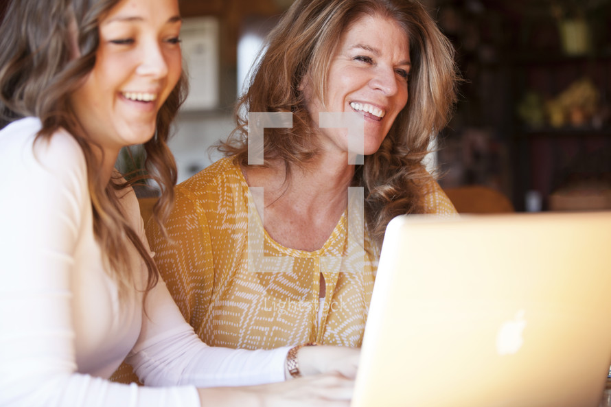 Mother and daughter laughing while working at a laptop computer.