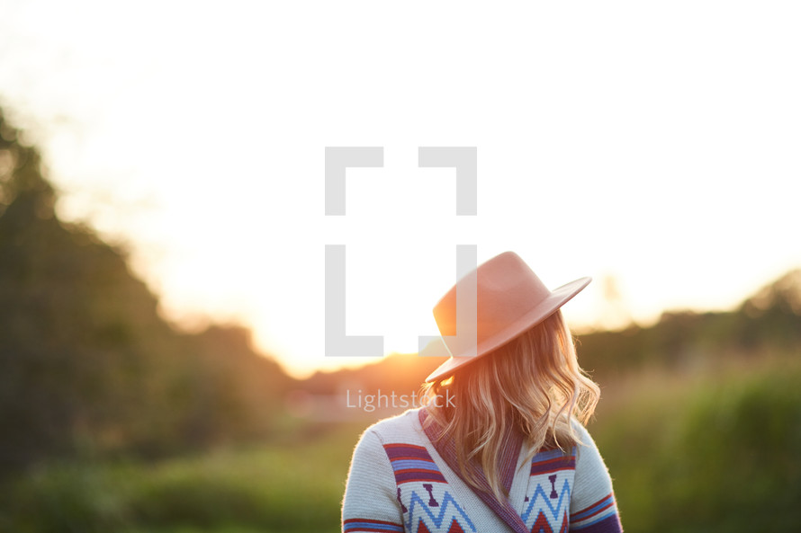 woman in a hat and sweater standing outdoors in sunlight