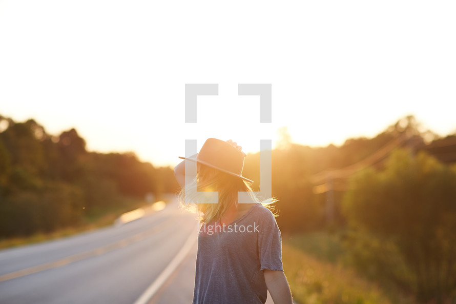 a woman in a hat standing on the side of a road