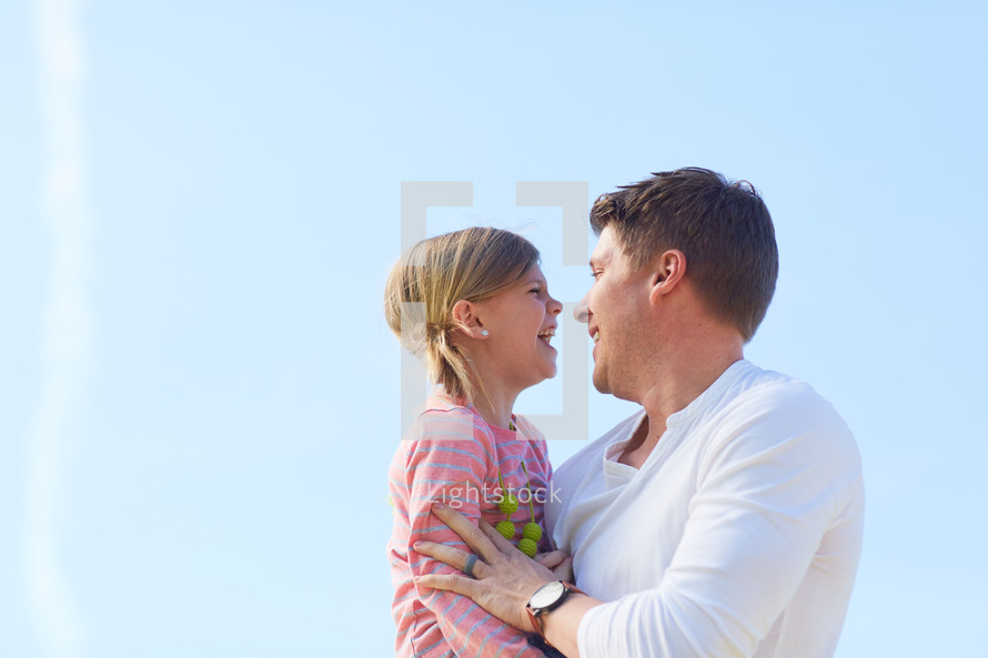 a farther holding his daughter outdoors