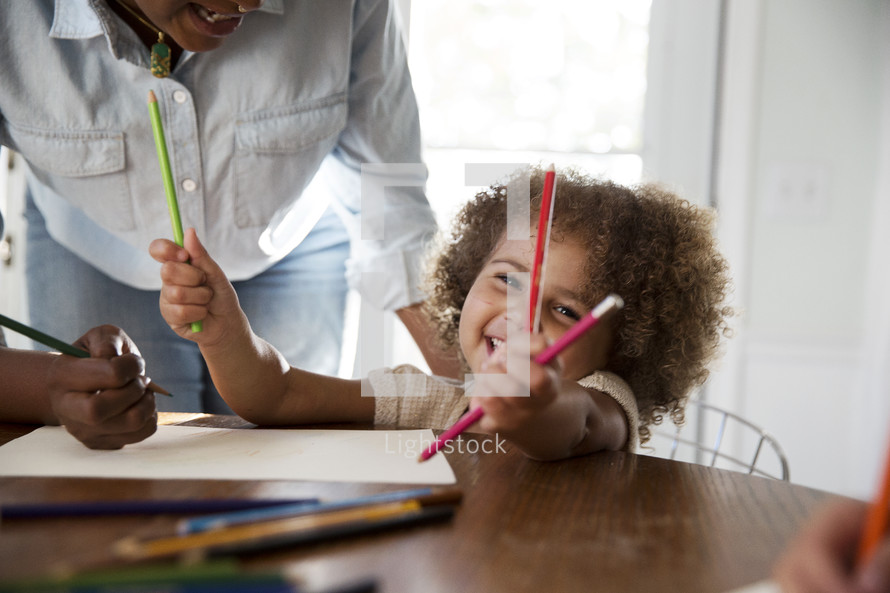children coloring with mom at the kitchen table