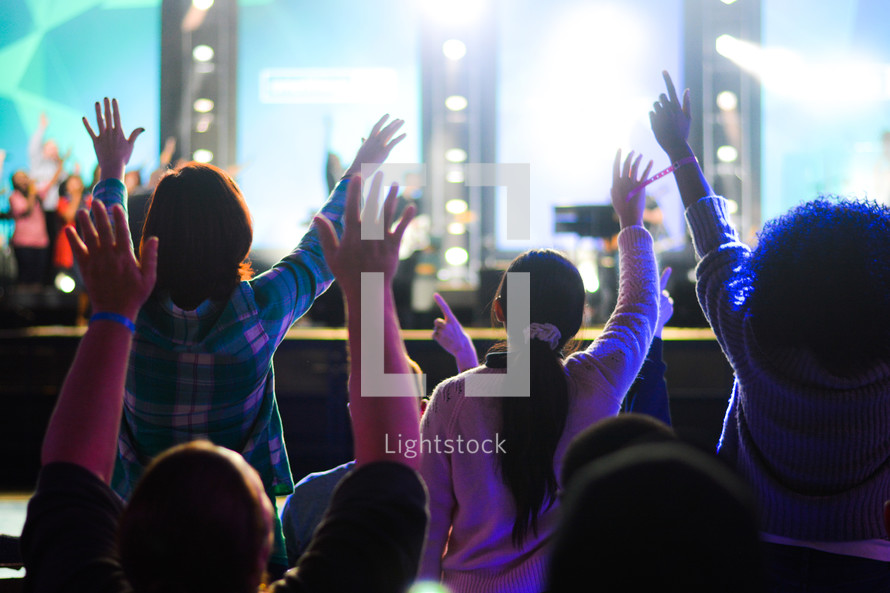 girls standing with raised hands at a worship service
