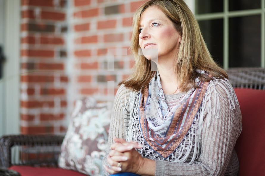 a woman sitting on a porch praying