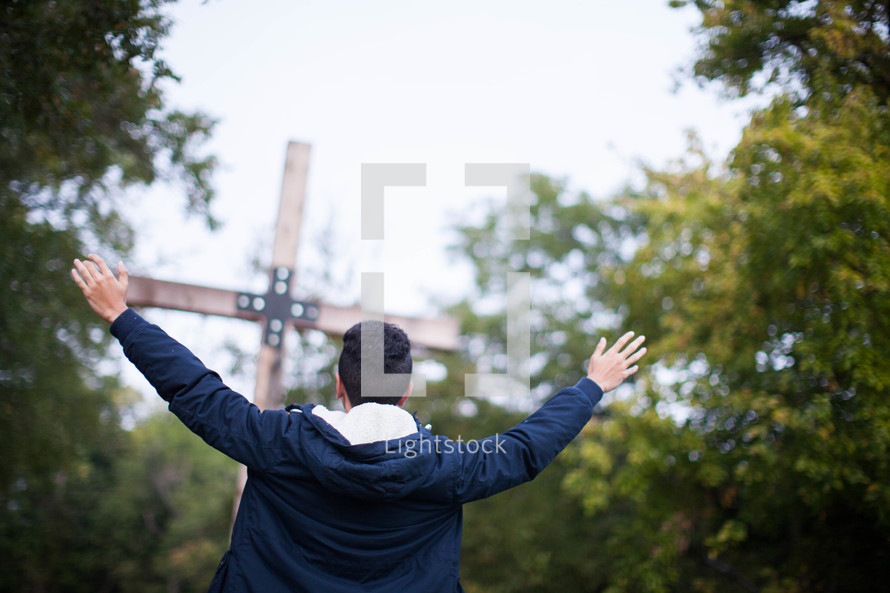 teen boy standing with raised hands in front of a wood cross