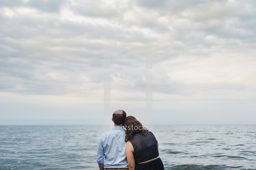 a couple standing on the beach looking out at the ocean