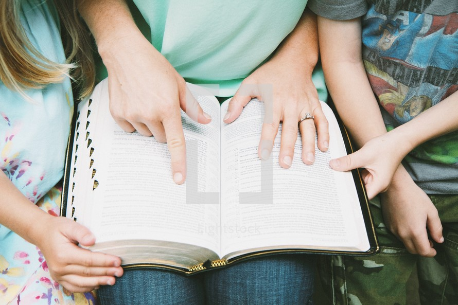 mother reading a Bible to her children