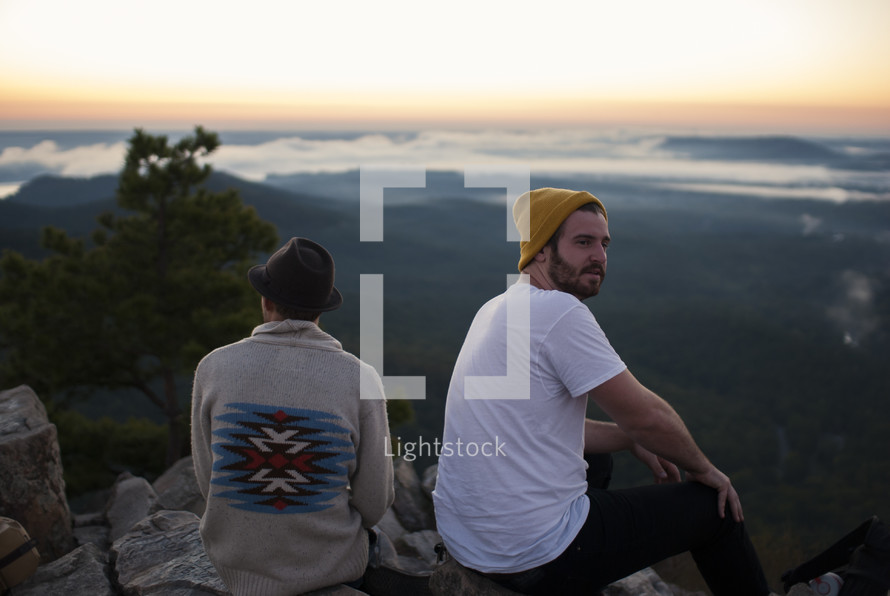 friends sitting on top of a mountain