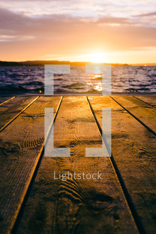 wood boards on a dock at sunset