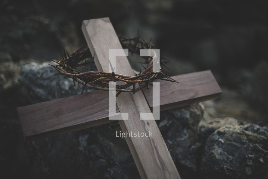 wooden cross with crown of thorns on a rock