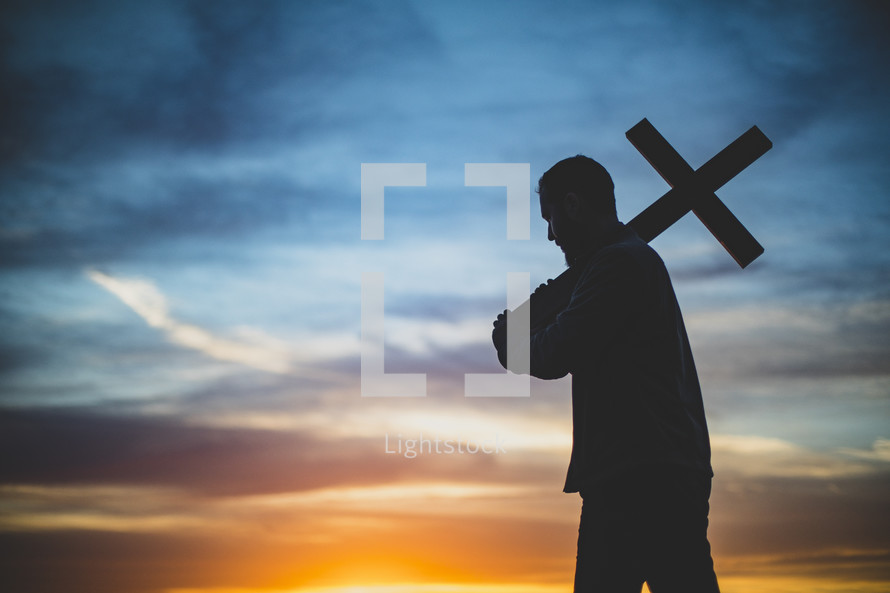 silhouette of a man holding up a cross at sunset