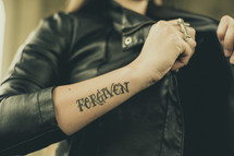woman in a leather jacket with a tattoo of the word Forgiven
