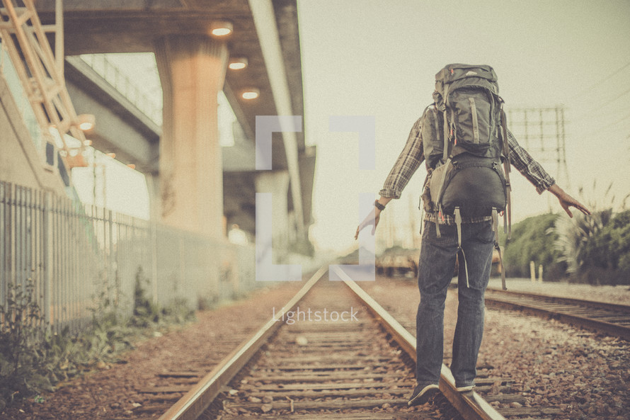 man balancing walking on railroad tracks with a backpack