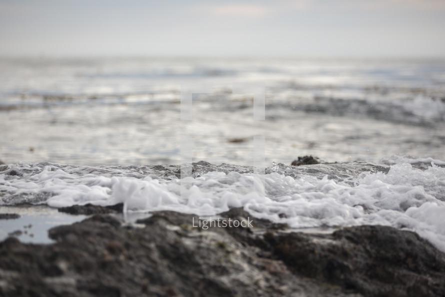 Foam of the ocean waves on the beach.