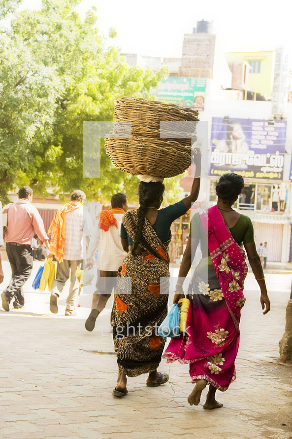 Woman in India carrying baskets on her head.