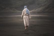Jesus walking barefoot on a beach