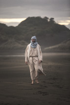 biblical figure walking on a beach