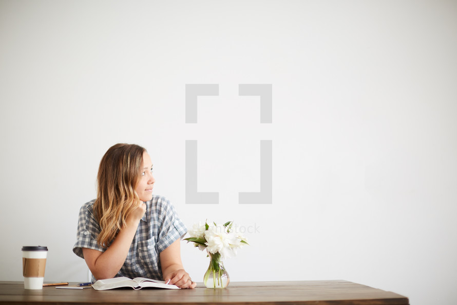 a woman sitting at a table in a coffee shop reading a Bible