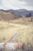 Woman laying in a field of grass, reading the Bible.