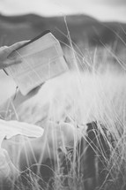 Woman laying outside in a field of grass reading the Bible.