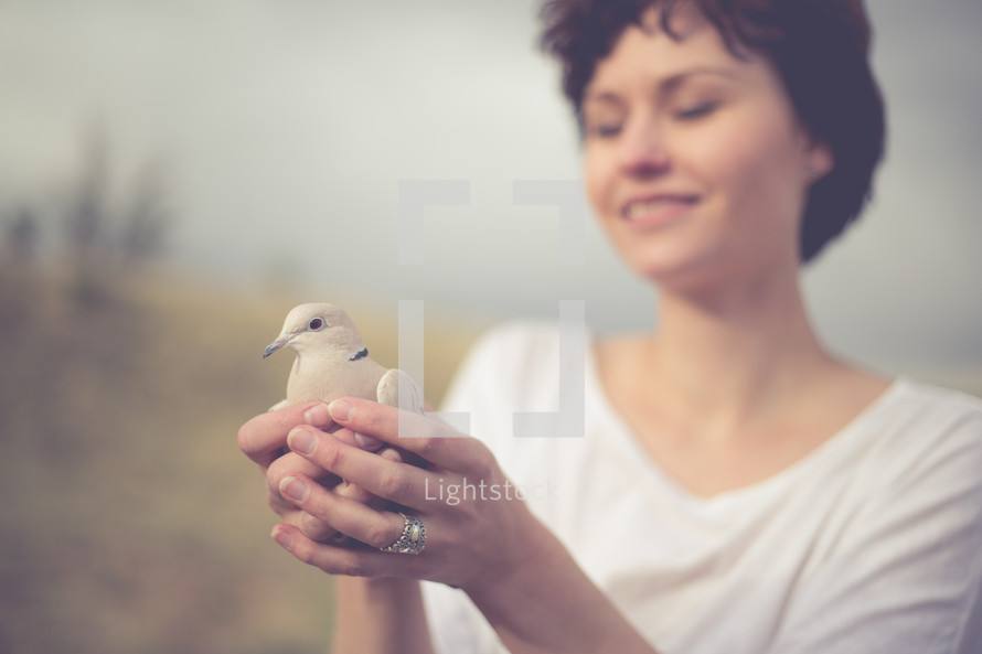 Smiling woman holding a dove.