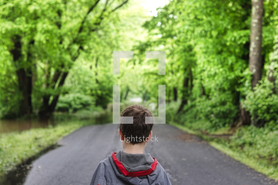 a boy standing alone on a rural road