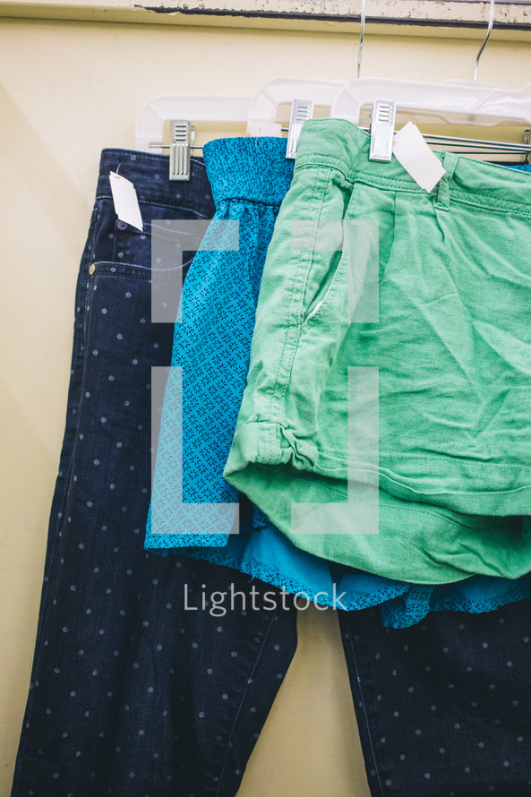 shorts and pants on the rack at a second hand shop