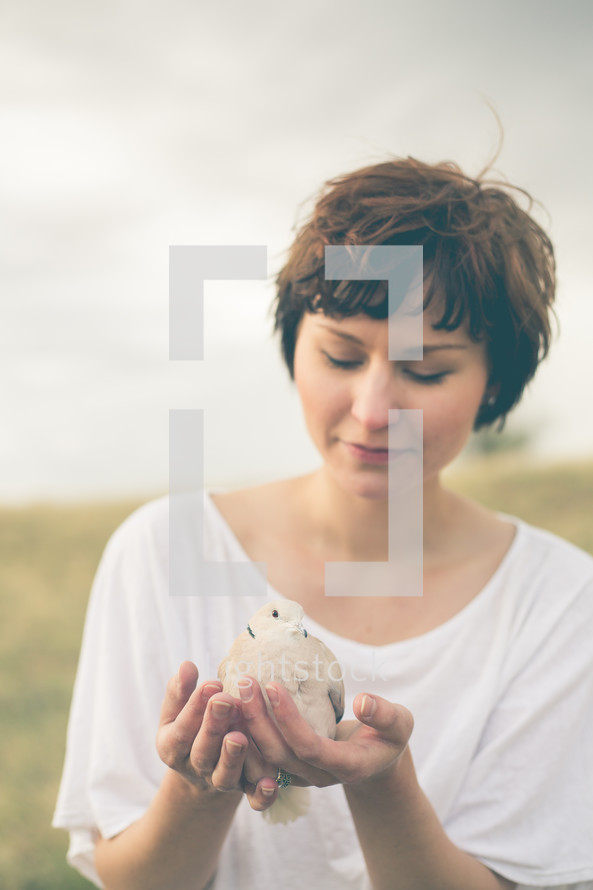 Woman holding a dove outside.