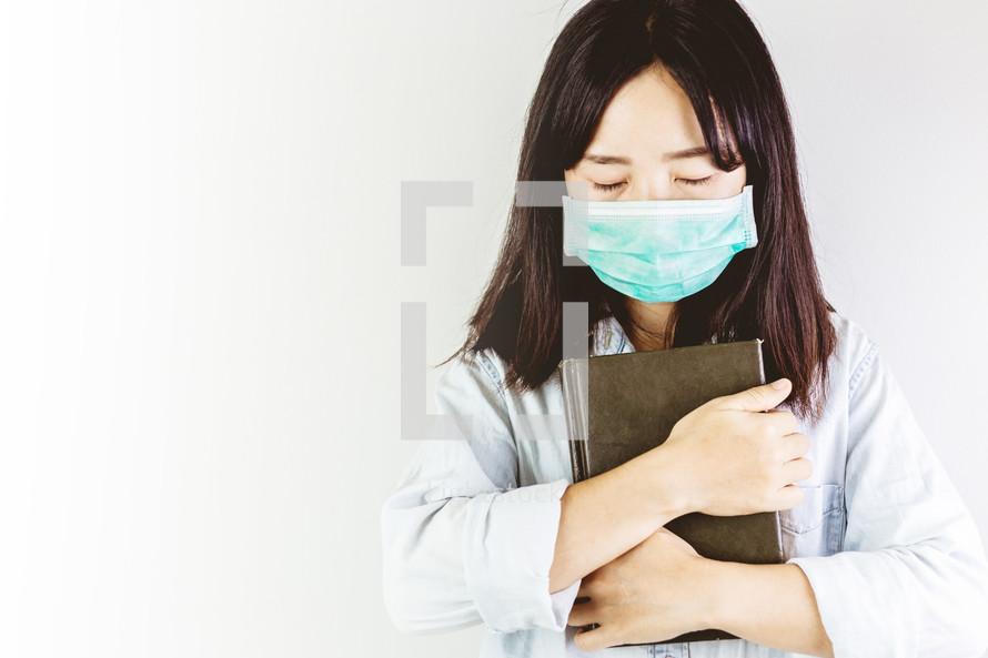 a woman wearing a mask praying holding a Bible