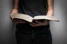 torso of a young woman in jeans and a tank top reading a Bible