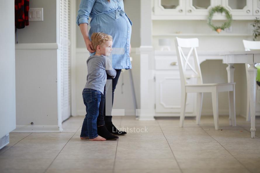 toddler boy hugging mom's leg