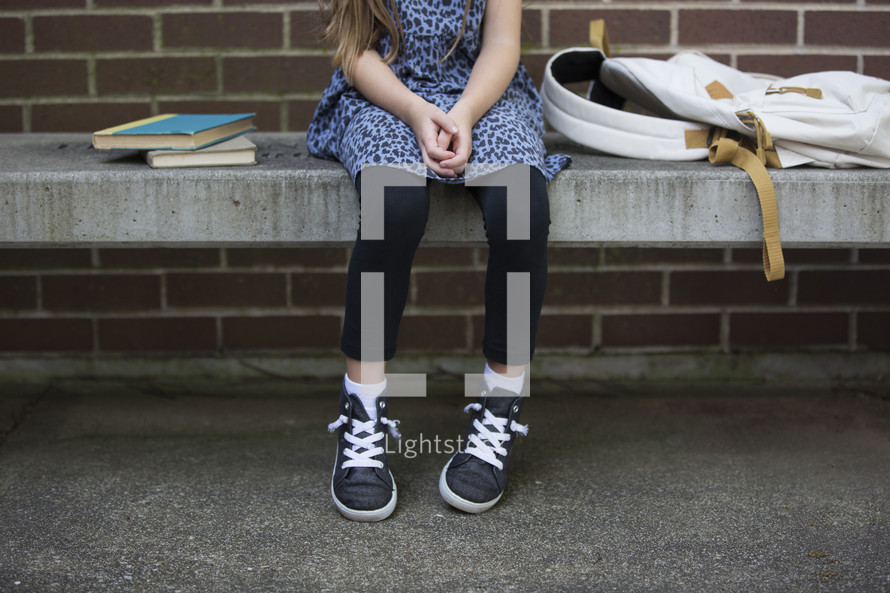 a child sitting on a bench waiting for school