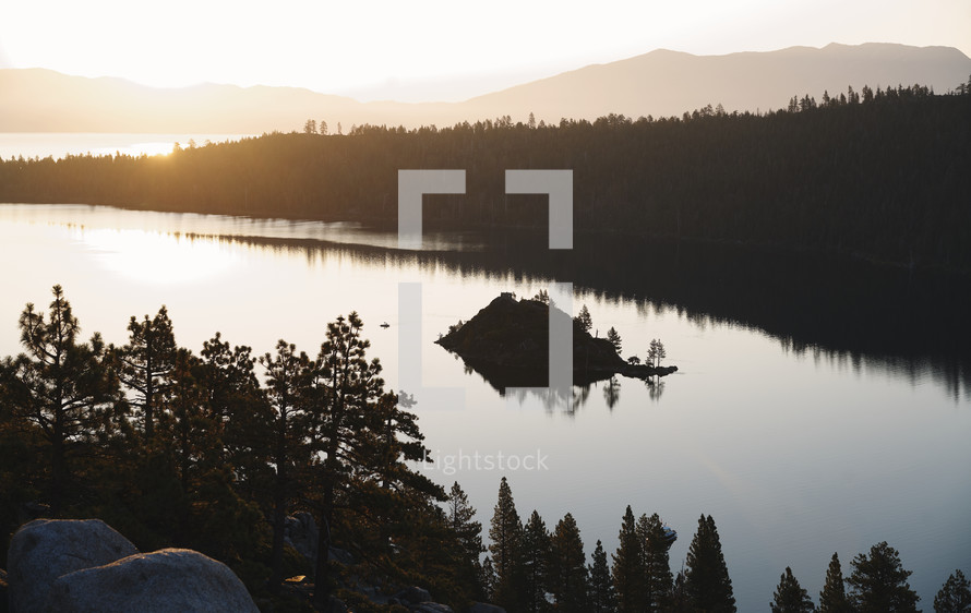 A lake and a forest with mountains in the background during sunrise