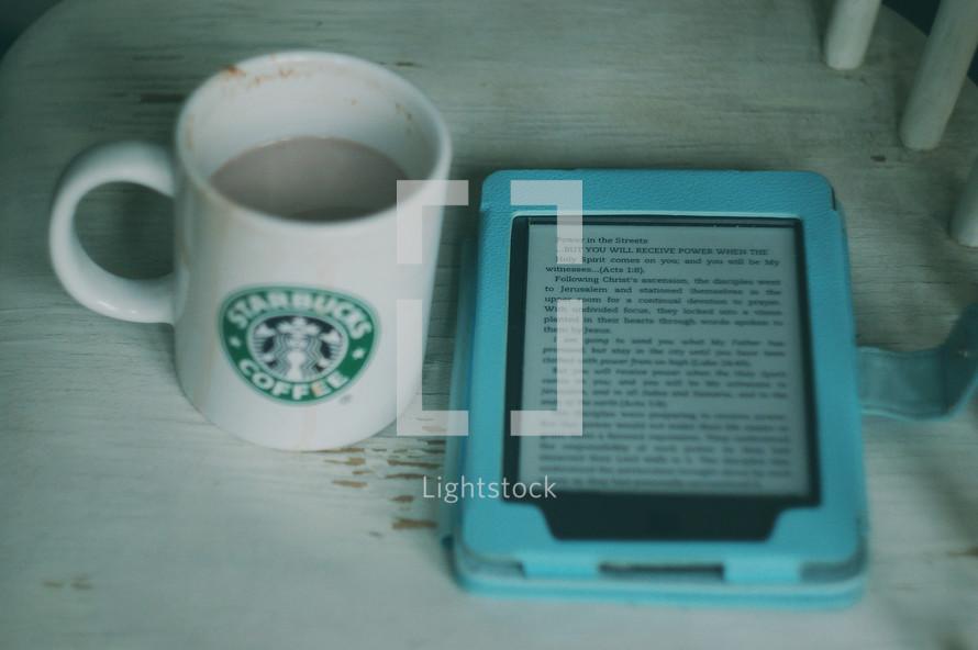 Starbucks coffee mug and Bible app on a tablet