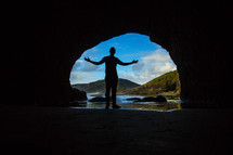 silhouette of a man in the entrance of a cave