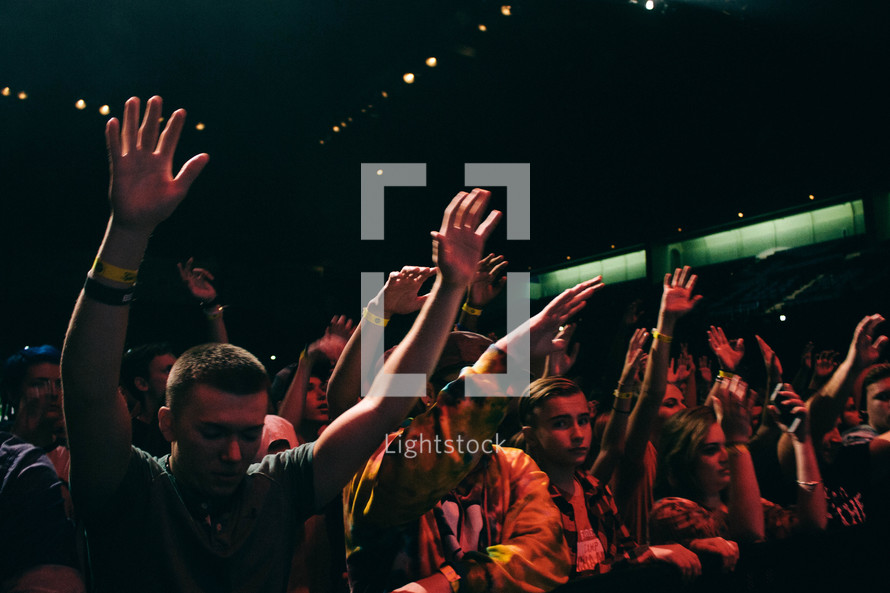 youth in the crowd at a youth rally with raised hands