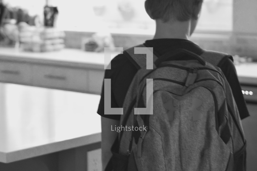 a middle school student with a backpack standing in a kitchen ready for school