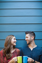 A young man and woman drinking coffee together near a blue wall.